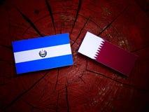 与Qatari旗子的El萨尔瓦多的旗子在被隔绝的树桩 库存图片