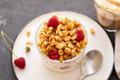 与rasberries的新鲜的在清楚的玻璃的酸奶和咖啡 在白色碗的莓 健康早晨早餐 免版税库存照片
