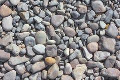 与reeble干燥灰色圆的大和小的海的抽象背景 免版税库存图片