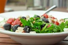 与ruccola,蕃茄,杉木仁的新鲜的希腊样式沙拉 库存照片