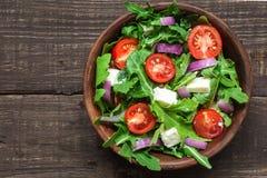 与rucola、蕃茄樱桃,希腊白软干酪和红洋葱的新鲜的mixd沙拉在土气木桌上的一个碗 顶视图 库存照片
