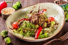 与rucola,甜椒,蕃茄,夏南瓜,硬花甘蓝,抱子甘蓝,芦笋,在木背景的大豆的健康沙拉 免版税库存图片
