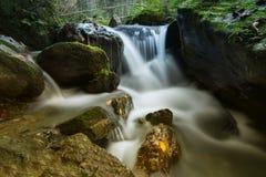 与samall瀑布的秋天小河 免版税库存照片