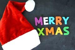 与Santa's红色帽子的快活的Xmas五颜六色的文本在黑暗的背景 库存图片