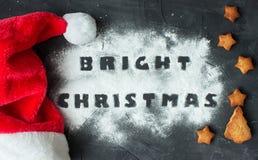 与Santa& x27的圣诞节背景; s盖帽和被烘烤的姜饼星和圣诞树与做的词明亮的圣诞节 图库摄影