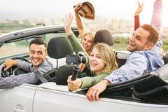 与selfie的愉快的朋友照相在假期黏附在敞篷车汽车-年轻人的照相机获得乐趣在敞蓬车汽车 免版税库存照片