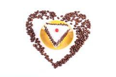 与sesa的心形的咖啡豆围拢的可口蛋糕 免版税图库摄影