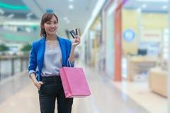与shoppi的亚洲妇女购物微笑和藏品购物袋 库存图片