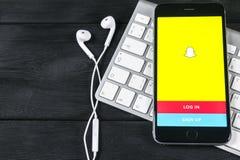 与Snapchat主页的苹果计算机iPhone 7在显示器屏幕上 Snapchat是社会网络网站 Snapchat主页  聪明的com 免版税库存照片