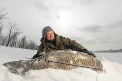 与speargun的Spearfishing射击了一条大鱼在河下伏尔加河的冰 免版税图库摄影