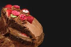 与strawberrys的自创巧克力蛋糕在黑色 免版税库存图片