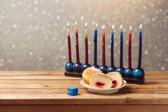 与sufganiyah的犹太在木桌上的假日光明节和menorah在bokeh背景