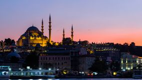 与Suleymaniye清真寺的伊斯坦布尔都市风景有游人的在晚上运输漂浮在Bosphorus 免版税库存图片