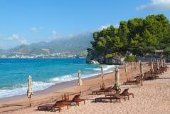 与sunbeds和被关闭的伞的离开的海滩 免版税库存图片