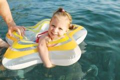 与swimring的愉快的微笑的小女孩游泳在海 免版税图库摄影