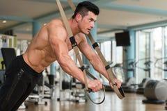 与Trx健身皮带的年轻有吸引力的人训练 免版税库存图片