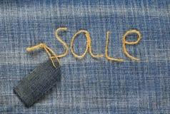 与twi题字销售的时髦的牛仔布织品背景  库存图片