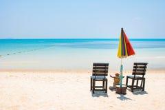与umbrela在白色沙子海滩和蓝色海的两把椅子同样的 库存照片