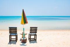 与umbrela在白色沙子海滩和蓝色海的两把椅子同样的 免版税图库摄影