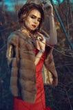 与updo头发的迷人模型和美丽做站立在干燥秋天树的佩带的红色礼服在黎明 免版税库存图片