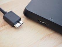 与usb3连接器的黑USB缆绳在与高速数据传送概念的木头上 库存照片