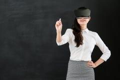 与VR耳机的亚洲妇女老师文字白垩 库存图片