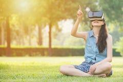 与VR耳机的美好的亚洲妇女接触scrrn 库存照片