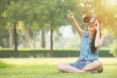与VR耳机的美好的亚洲妇女接触scrrn 免版税库存图片
