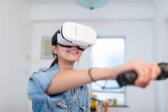 与VR设备的亚洲妇女戏剧在家 图库摄影
