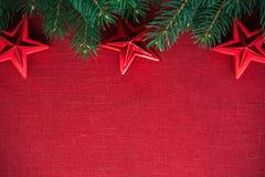 与xmas树的在红色帆布背景的框架和装饰品 圣诞快乐看板卡 库存照片