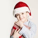 与Xmas礼物盒的圣诞节孩子 有红色圣诞老人帽子的儿童男孩 免版税库存图片