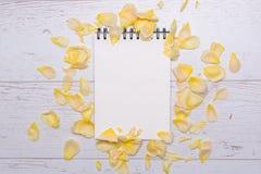与yelloy玫瑰花瓣的白皮书海报招呼的文本拷贝空间的 顶视图 平的位置 免版税库存图片