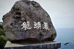 与Yongduam岩石,龙顶头岩石的题字的石头在济州,韩国 免版税库存图片