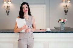 专业不动产房地产经纪商显示时髦的现代议院 她在拿着纸的桌附近站立 图库摄影