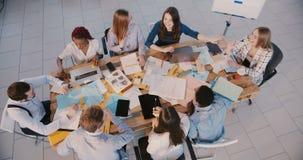 专业不同种族的愉快的年轻新运作公司伙伴谈论工作在现代办公室,配合顶视图 影视素材