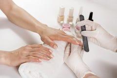 专业与文件的美容师擦亮的手指钉子在秀丽修指甲演播室 免版税库存照片