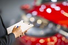 专业人员saleman企业在笔记薄或书,纸的检查文字有汽车模糊的背景 对运输汽车autom 免版税库存照片