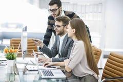专业企业队在一个现代办公室开发一个新的项目,坐在一张书桌后 图库摄影