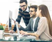 专业企业队在一个现代办公室开发一个新的项目,坐在一张书桌后 免版税库存照片
