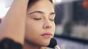 专业化妆师在工作:应用在少妇` s皮肤的女性手特写镜头视图面部粉末使用 股票录像