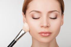 专业化妆师是对待有吸引力 免版税库存照片