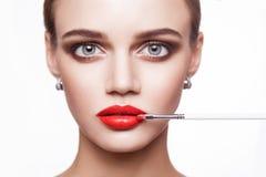 专业化妆师申请美丽的少妇的构成有蓝眼睛和浅褐色的发型和完善的皮肤的 库存照片