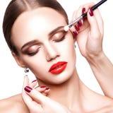专业化妆师申请美丽的少妇的构成有蓝眼睛和浅褐色的发型和完善的皮肤的 免版税库存图片