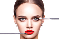专业化妆师申请美丽的少妇的构成有蓝眼睛和浅褐色的发型和完善的皮肤的 库存图片