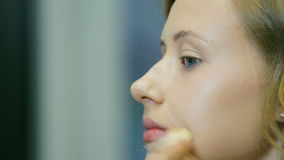 专业化妆师适用于音调的奶油的白肤金发的长的卷毛头发和蓝眼睛塑造皮肤 影视素材