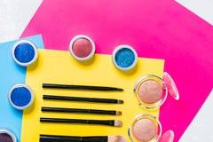 专业化妆用品,构成刷子 眼影膏在明亮的黄色,桃红色背景,顶视图,特写镜头中 库存图片