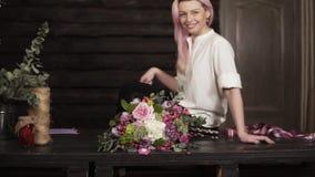 专业卖花人做的惊人的花束的美好的慢动作英尺长度诱人,白色衬衣的微笑的女孩 股票录像