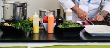 专业厨师切口成份和一块白色板材为一顿可口膳食做准备 库存图片