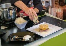 专业厨师刺耳乳酪和一块白色板材的手为一顿可口膳食做准备 库存照片