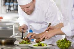 专业厨师在餐馆准备牛排盘 免版税库存照片
